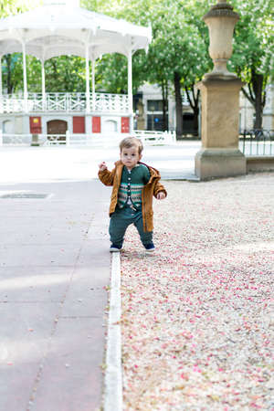 A year and a half old baby taking his first steps in a park with a loose stone floor, he is learning to walk