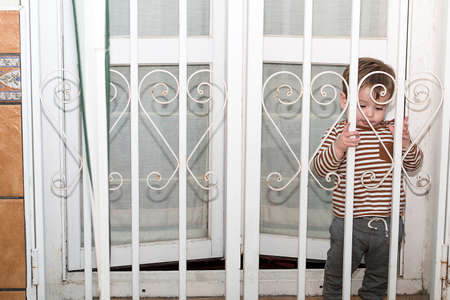 A year and a half old boy wanting to go out to his terrace in the quarantine, he has his fence closed. 版權商用圖片