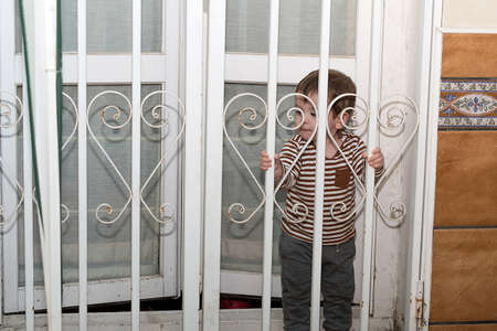 A year and a half old boy wanting to go out to his terrace in the quarantine, he has his fence closed. 免版税图像