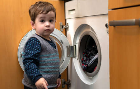 Child helping to set up the washing machine to do the laundry. He puts the clothes in the vat.