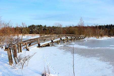 A wooden bridge over a frozen river photo