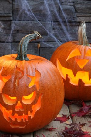 Carved pumpkins, lit with brick and spider web background