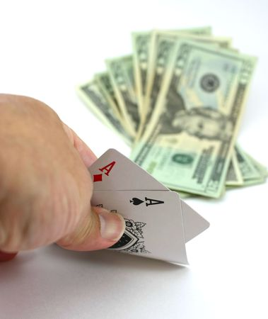 Poker player views pocket pair aces, cash bet in the background Stock Photo - 6057331