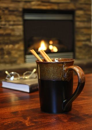 Hot cinnamon tea, warm relaxing environment by the fireplace photo