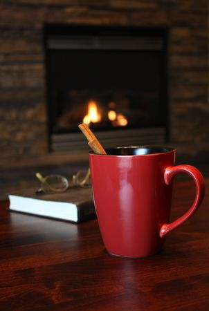 Cinnamon tea by the fire, warm and relaxing setting photo