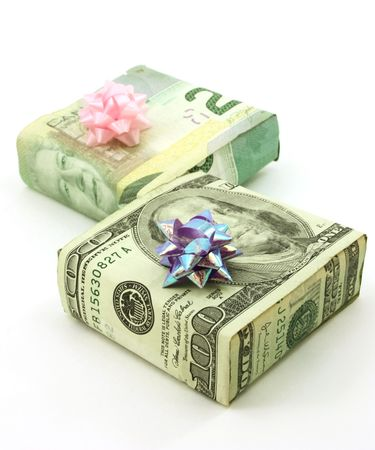 Dollars wrapped around two gifts with bows, isolated photo