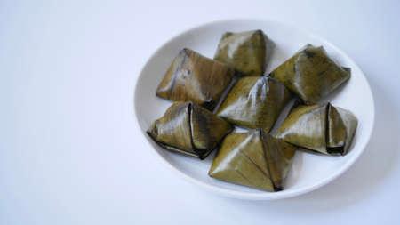Stuffed dough pyramid dessert called Ka-Nhom-Tian isolated on black background, Thai dessert wrapped in banana leaves