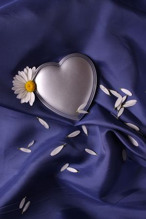 Silver heart on a sheet of blue satin caressly draped photo