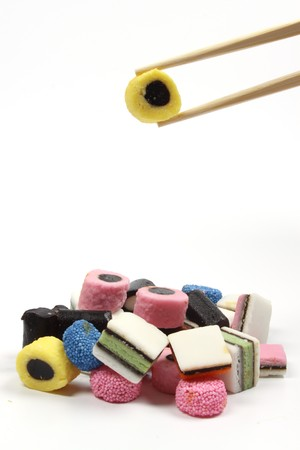 Eating Colorful liquorice candy with Asian chopsticks photo