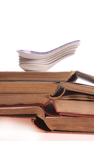 Chinese spoons on a pile of old prescription-books isolated against a white background with copy space