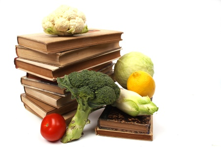 Old cookbooks with several vegetables isolated against a white background
