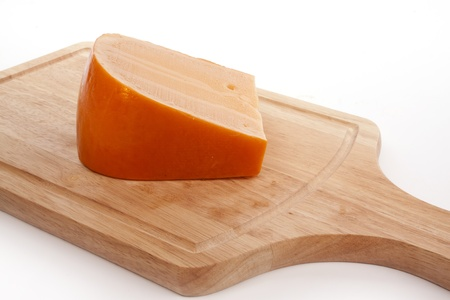 Cheese on a cutting board against a white background Stock Photo