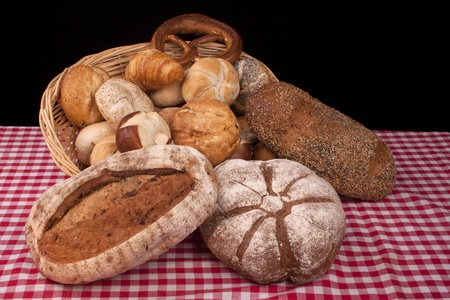 breadloaf: Various bread rolls and buns on a dressed table
