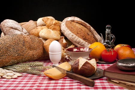 Old fashioned lunch wtih bread and buns on a table against a black background photo