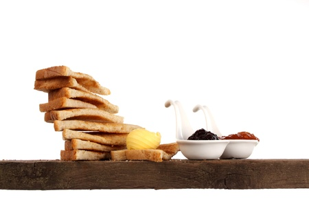 Various kinds of bread loaf and buns on a shelf in a studio setting photo
