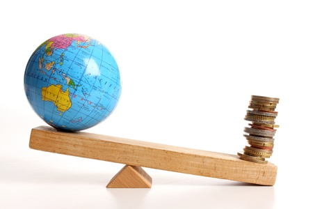 Weighing the earth on a wooden balance Stock Photo