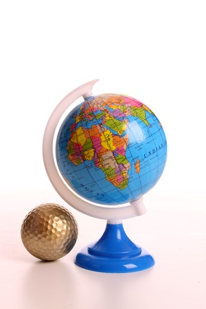 A golden golf ball and the world on a globe photo