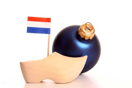 Clogs,flag and a christmas baulbe against a white background photo