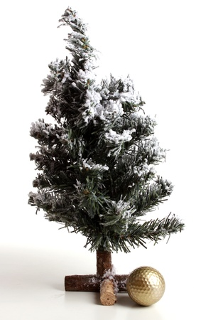 christmas golf: Christmas tree with golf ball over white in a studio