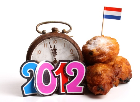 An Oliebol is typical Dutch  and a clock  approaching the New Year 2012 over white  photo