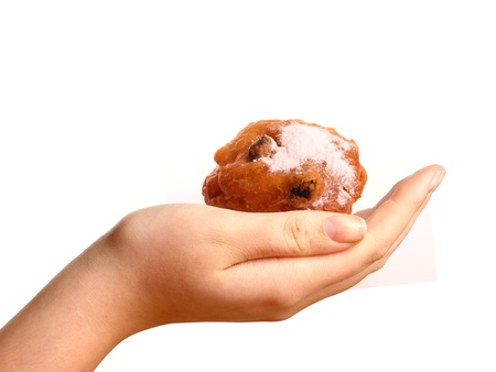 An Oliebol in a young womans hand photo