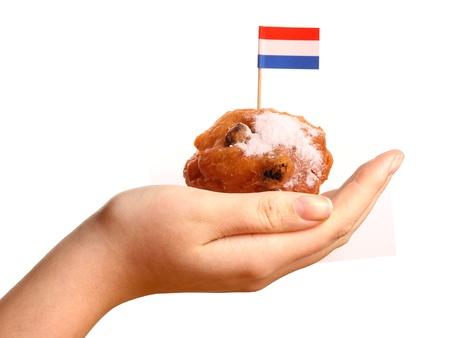 Een Oliebol met een Nederlandse vlag in een jonge womans hand