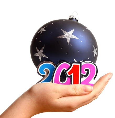Young womans hand for New Year 2012 and a bauble in the studio photo