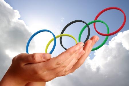 deportes olimpicos: Anillos olímpicos en las manos de los womans jóvenes contra el cielo