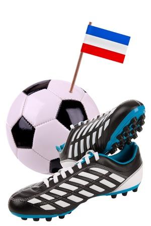 reps: Un par de tacos o botas de f�tbol con una peque�a bandera de Yugoslavia Reserva Federal. Rep. Foto de archivo