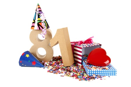 81: Number of age in a colorful studio setting with paper party hats, a red heart and gifts on a bottom of confettie Stock Photo