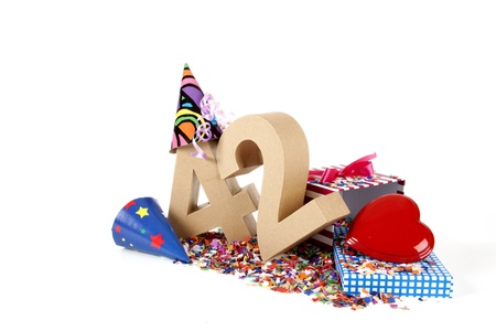 Number of age in a colorful studio setting with paper party hats, a red heart and gifts on a bottom of confettie 写真素材