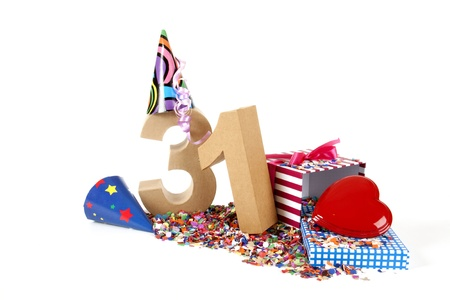 31: Number of age in a colorful studio setting with paper party hats, a red heart and gifts on a bottom of confettie Stock Photo
