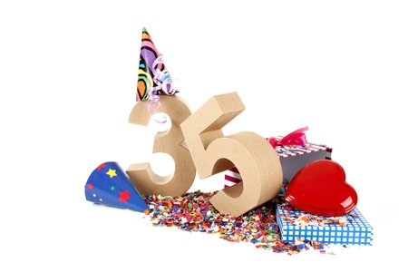 age 30 35 years: Number of age in a colorful studio setting with paper party hats, a red heart and gifts on a bottom of confettie Stock Photo
