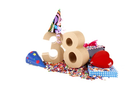 38: Number of age in a colorful studio setting with paper party hats, a red heart and gifts on a bottom of confettie Stock Photo
