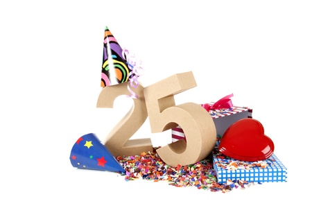 five year: Number of age in a colorful studio setting with paper party hats, a red heart and gifts on a bottom of confettie Stock Photo