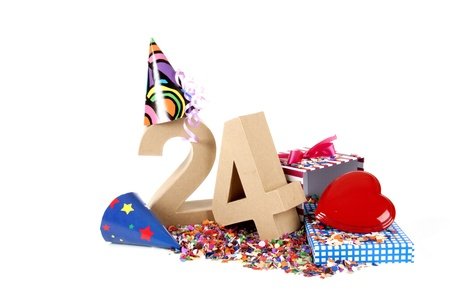 Number of age in a colorful studio setting with paper party hats, a red heart and gifts on a bottom of confettie Stock Photo - 16598371