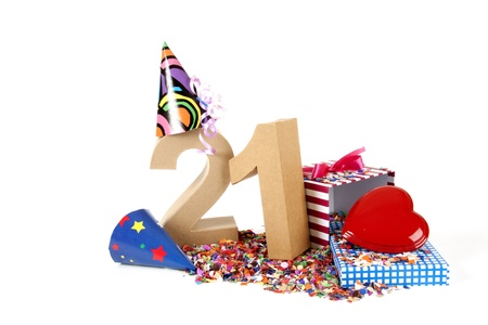 21: Number of age in a colorful studio setting with paper party hats, a red heart and gifts on a bottom of confettie Stock Photo