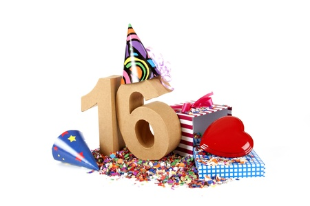 number 16: Number of age in a colorful studio setting with paper party hats, a red heart and gifts on a bottom of confettie Stock Photo