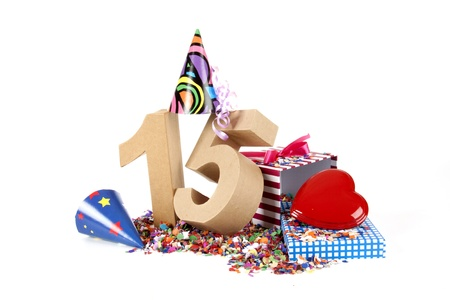10 15 years: Number of age in a colorful studio setting with paper party hats, a red heart and gifts on a bottom of confettie Stock Photo