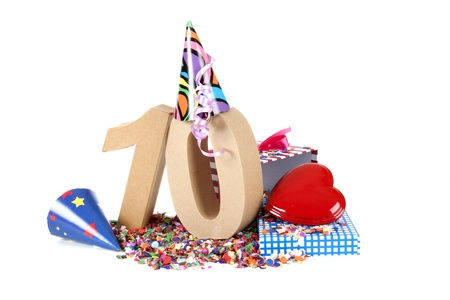 Number of age in a colorful studio setting with paper party hats, a red heart and gifts on a bottom of confettie Reklamní fotografie