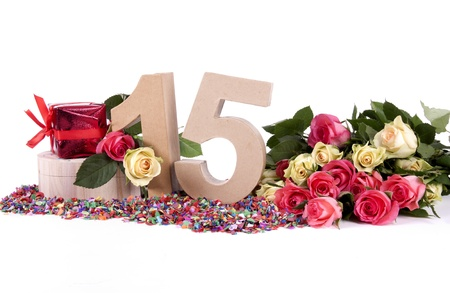 number 15: Number of age in a colorful studio setting with fresh roses on a bottom of confetti