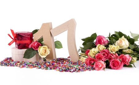 seventeen: Number of age in a colorful studio setting with fresh roses on a bottom of confetti