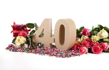 Aantal leeftijd in een kleurrijke studio omgeving met verse rozen op een bodem van confetti Stockfoto