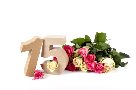 number 15: Number of age in a colorful studiosetting,surrounded with roses
