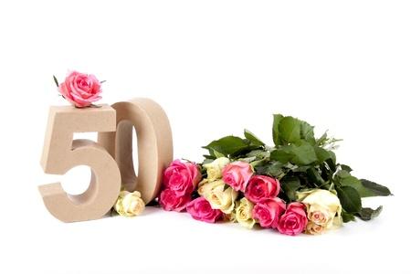 Aantal leeftijd in een kleurrijke studiosetting, omringd met rozen Stockfoto
