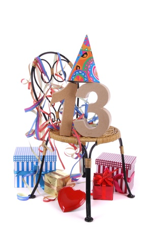 Number of age in a colorful studio setting with paper party hat and figures, a red heart and gifts photo
