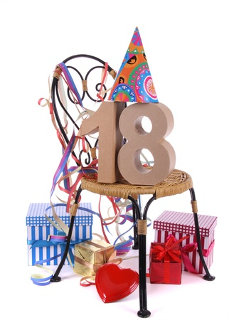 18: Number of age in a colorful studio setting with paper party hat and figures, a red heart and gifts