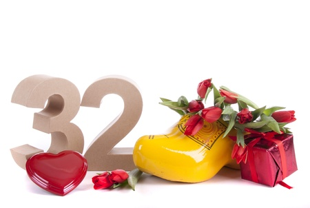 Number of age in a colorful studio setting and Dutch looking attributes like a clog woonden shoe and tulips photo