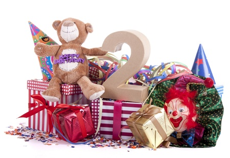 Number of age in a colorful studio setting with paper party hats, a red heart and gifts on a bottom of confetti for  childrens birthday party     photo