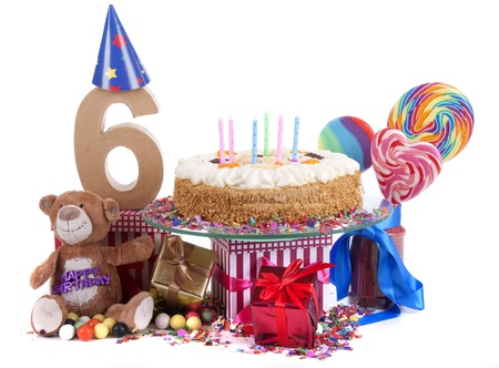 Number of age in a colorful studio setting with paper party hats, a red heart and gifts on a bottom of confetti and sweet cake with candles Stock Photo - 17296547
